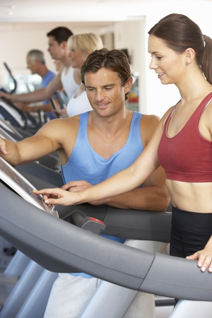 keeping fit: Woman Working With Personal Trainer On Running Machine In Gym