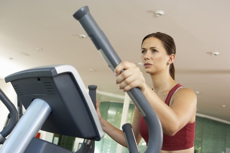 keeping fit: Woman On Cross Trainer Machine In Gym Stock Photo