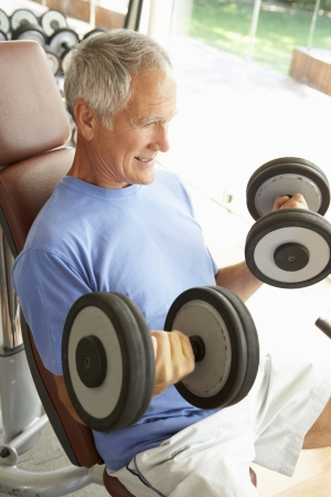 levantar peso: Senior Man trabajo con pesas en el gimnasio