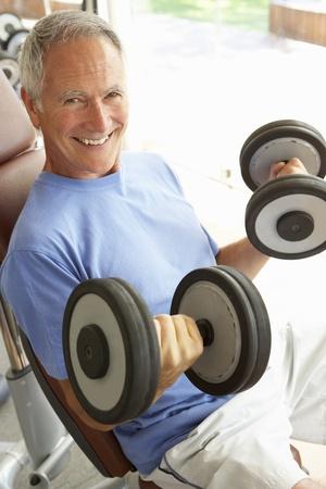 levantar peso: Senior hombre trabajando con pesas en el gimnasio