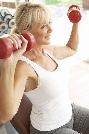 levantando pesas: Mujer Senior trabajo con pesas en el gimnasio Foto de archivo