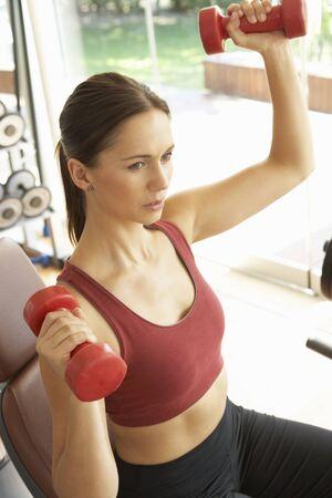 levantando pesas: Mujer joven trabajando con pesas en el gimnasio