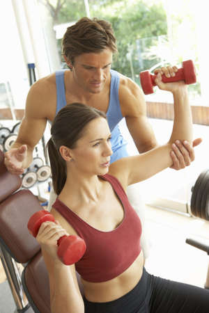 Young Woman Working With Weights In Gym With Personal Trainer Stock Photo - 8505088
