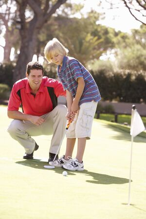 Father Teaching Son To Play Golf On Putting On Green Stock Photo - 8510106