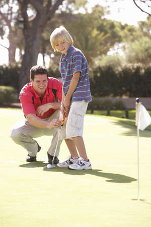 putting: Father Teaching Son To Play Golf On Putting On Green