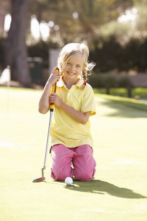 Young Girl Practising Golf On Putting On Green photo