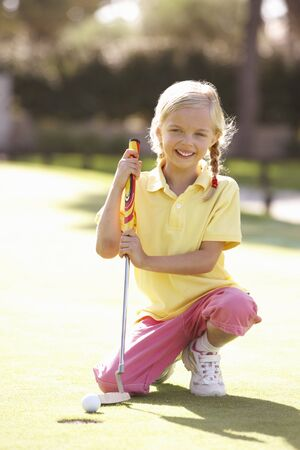putting green: Young Girl Practising Golf On Putting On Green Stock Photo