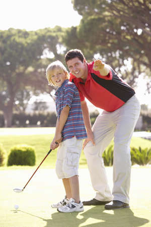 Father Teaching Son To Play Golf On Putting On Green photo