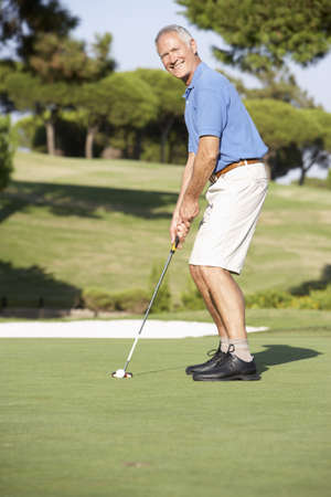 Senior Male Golfer On Golf Course Putting On Green photo