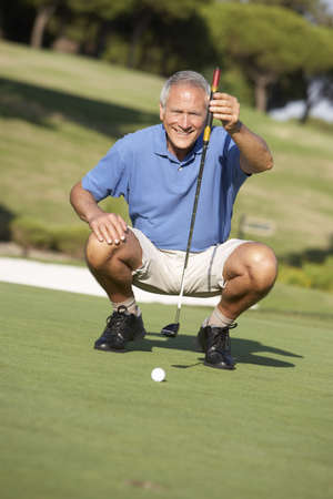 Senior Male Golfer On Golf Course Lining Up Putt On Green photo