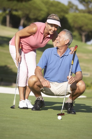 Senior Couple Golfing On Golf Course Lining Up Putt On Green photo
