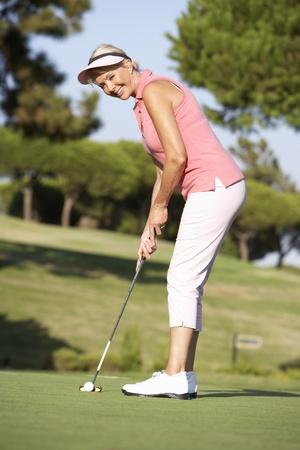 Senior Female Golfer On Golf Course Lining Up Putt On Green photo
