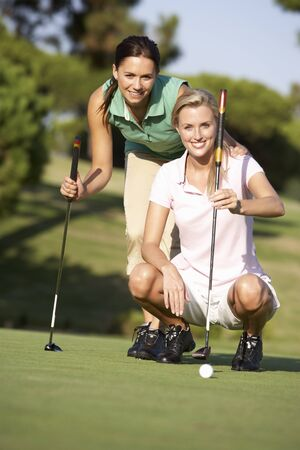 Two Female Golfers On Golf Course Lining Up Putt On Green photo