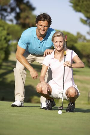 Couple Golfing On Golf Course Lining Up Putt On Green photo