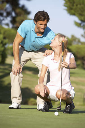 woman golf: Couple Golfing On Golf Course Lining Up Putt On Green