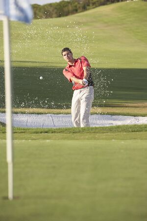 bunker: Male Golfer Playing Bunker Shot On Golf Course