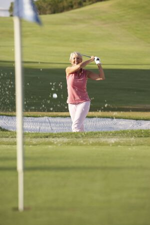 Senior Female Golfer Playing Bunker Shot On Golf Course photo