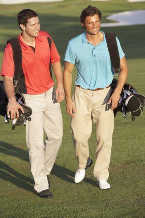 Two Men Walking Along Golf Course Carrying Bags photo