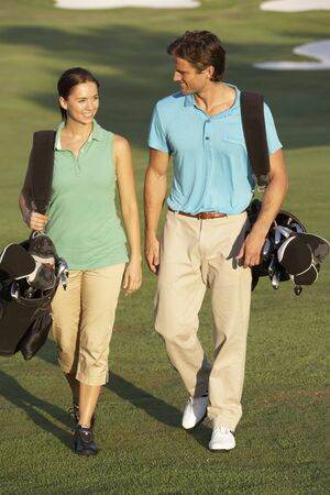 Couple Walking Along Golf Course Carrying Bags photo