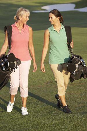 Two Women Walking Along Golf Course Carrying Bags photo
