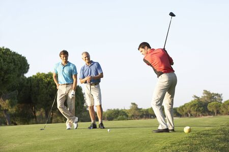 playing golf: Group Of Male Golfers Teeing Off On Golf Course Stock Photo