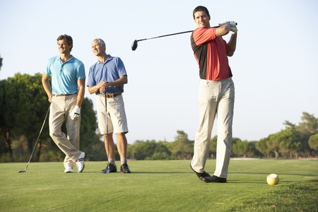 golf man: Group Of Male Golfers Teeing Off On Golf Course Stock Photo