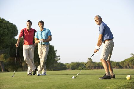 off course: Group Of Male Golfers Teeing Off On Golf Course Stock Photo
