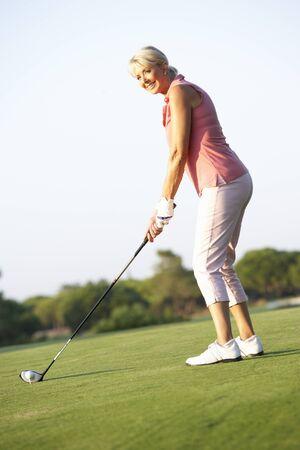 Senior Female Golfer Teeing Off On Golf Course Stock Photo - 8503490