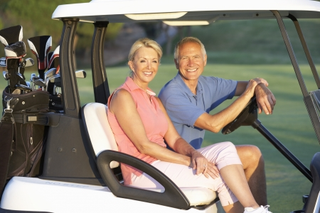 retired: Senior Couple Riding In Golf Buggy On Golf Course
