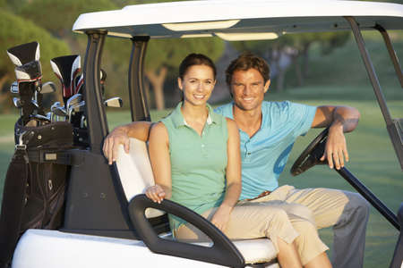 Couple Riding In Golf Buggy On Golf Course photo