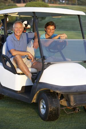 golf club: Two Male Golfers Riding In Golf Buggy On Golf Course Stock Photo