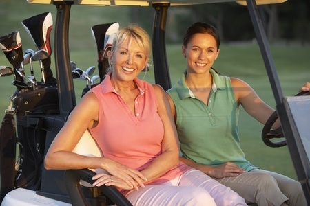 Two Female Golfers Riding In Golf Buggy On Golf Course photo