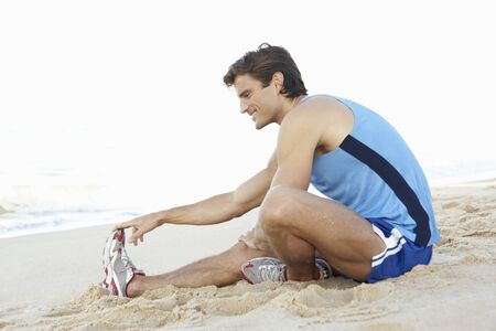 Young Man In Fitness Clothing Stretching On Beach Stock Photo - 8503470