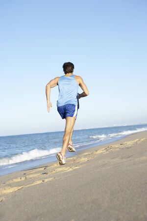 Young Man In Fitness Clothing Running Along Beach Stock Photo - 8502406