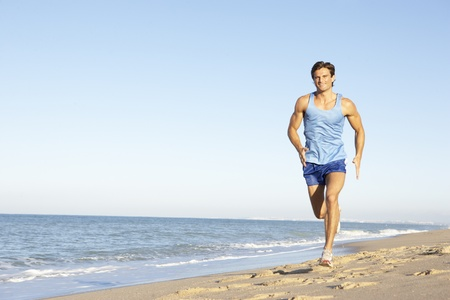 exercise man: Young Man In Fitness Clothing Running Along Beach