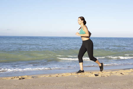 Young Woman In Fitness Clothing Running Along Beach Stock Photo - 8503572