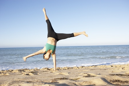 Young Woman In Fitness Clothing Turning Cartwheel On Beach Stock Photo - 8503655