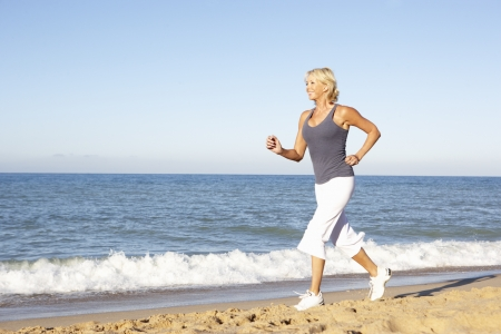 Senior Woman In Fitness Clothing Running Along Beach Stock Photo - 8503593