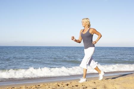 Senior Woman In Fitness Clothing Running Along Beach photo