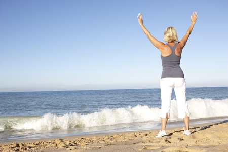 Senior Woman In Fitness Clothing Stretching On Beach Stock Photo - 8505153