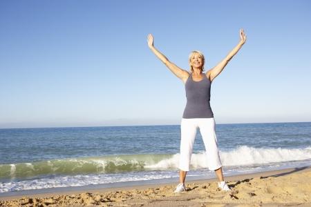 estiramientos: Mujer Senior en ropa de Fitness que se extiende en Playa Foto de archivo