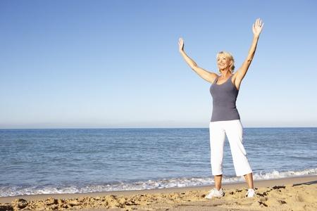 mujeres mayores: Mujer Senior en ropa de Fitness que se extiende en Playa Foto de archivo