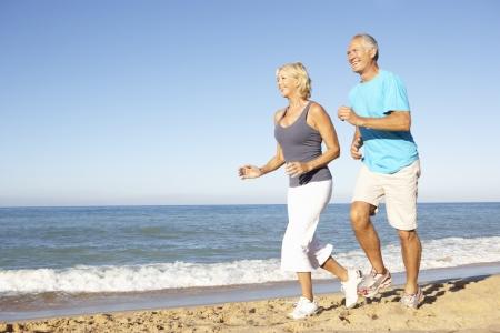 men exercising: Senior pareja en ropa de Fitness a lo largo de la playa