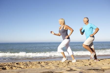 ジョグ: ビーチに沿って実行しているフィットネスの服の年配のカップル