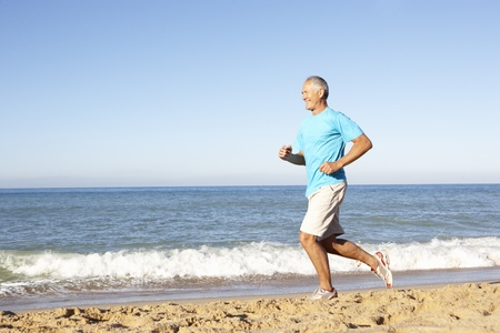Senior Man In Fitness Clothing Running Along Beach photo