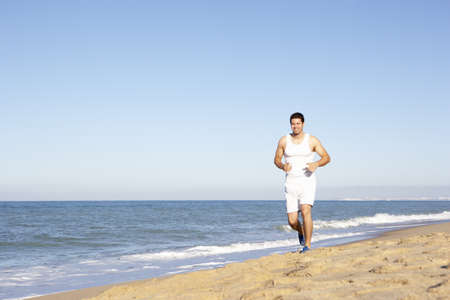 Young Man In Fitness Clothing Running Along Beach Stock Photo - 8502348