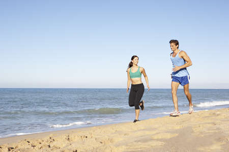Young Couple In Fitness Clothing Running Along Beach photo