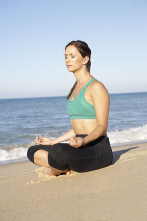 Young Woman In Fitness Clothing Meditating On Beach photo