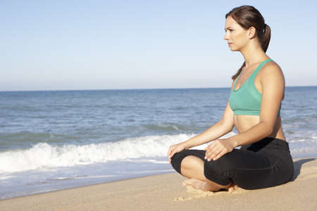 Young Woman In Fitness Clothing Meditating On Beach Stock Photo - 8503521
