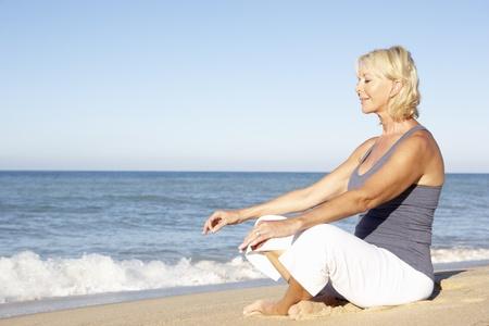 Senior Woman In Fitness Clothing Meditating On Beach Stock Photo - 8503499